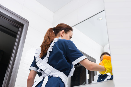 atomiser: Low angle view on maid in blue and white uniform in rubber gloves cleaning large bathroom mirror