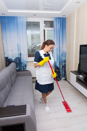 wall mounted: Housekeeper cleaning a hotel suite mopping the floor between a comfortable sofa and wall mounted television Stock Photo