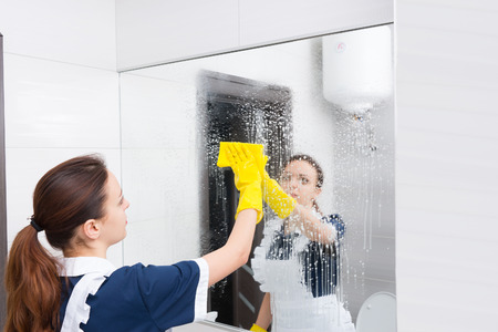 atomiser: Housekeeper or maid cleaning a large wall mirror in a white bathroom wiping it with a cloth after spraying it with detergent