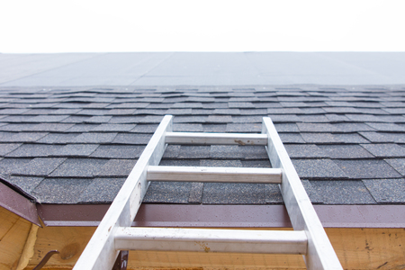 rungs: Ladder leading to an unfinished roof on a new house showing the installation of new roofing tiles and the waterproof membrane