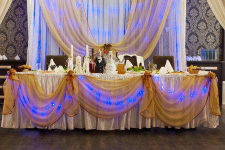 festooned: Empty glowing purple wedding party table with elegant furnishings along side dolls for bride and groom Stock Photo