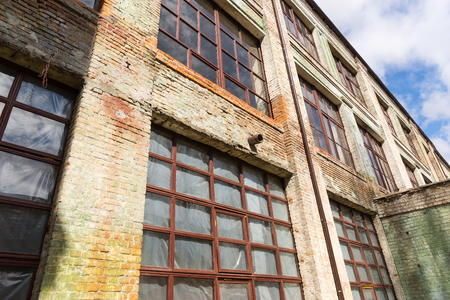 windowpanes: Exterior facade of a grungy old commercial building with large windows and stained brickwork viewed from below