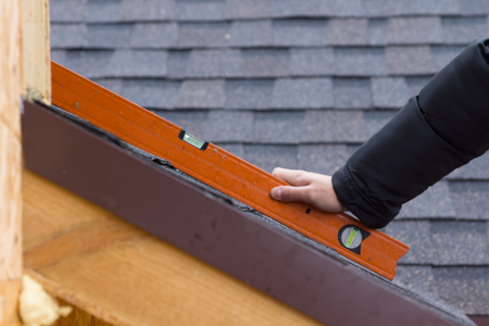 timber frame: Builder or roofer holding a spirit level over new roofing tiles on a timber frame house, close up of the tool and his hand