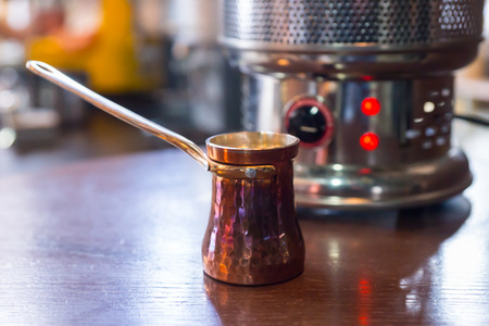 long handled: Special long handled jug for preparing the milk for cappuccino coffee on a counter in a restaurant in front of a coffee machine