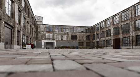 large doors: Ground level view from brick paving stones of old warehouse exterior with large windows and dock doors under gray cloudy sky Stock Photo