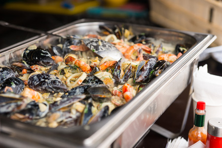 caterers: Delicious savory mixture of fresh mussels and seafood in a large metal catering dish keeping warm on a buffet at a catered event or hotel