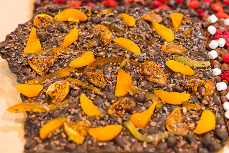 morsels: Close up view on yellow mango or peach fruit slices over chocolate and marshmallow pieces