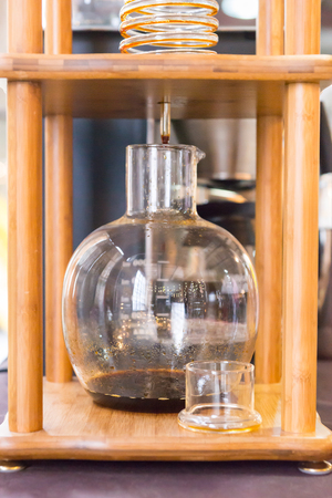 Close up on fancy polished yellow wooden and glass beaker and spiral coffeemaker Stock Photo