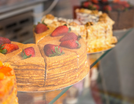 gateau: Delicious gourmet cakes and gateau displayed on glass shelves in a bakery window sliced ready for sale