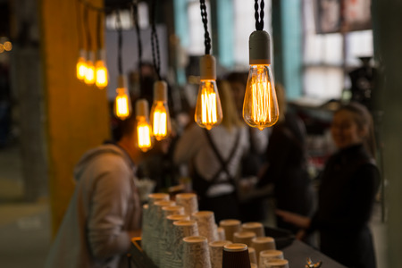 subdued: Selective focus view on bright yellow filaments inside bare light bulbs in crowded cafe with cups on counter Stock Photo