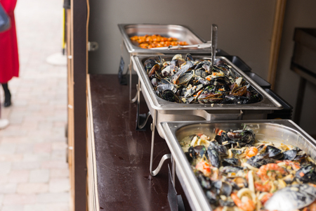 caterers: Assorted seafood on a buffet display displayed in metal bins with shellfish including mussels and prawns