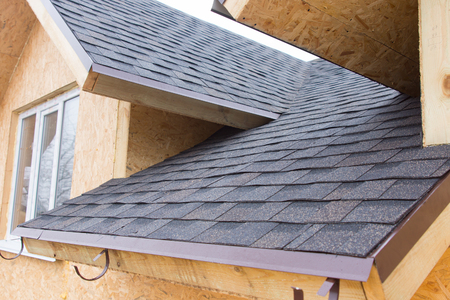 roofing membrane: Detail of overlapping roofing tiles on a new build wooden house with dormer windows Stock Photo