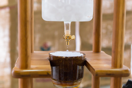 spigot: Close up on homemade coffee maker with spigot dripping liquid and glass cup surrounded by wooden parts Stock Photo
