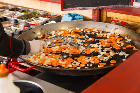 sautee: Cook stir frying fresh vegetables in a large pan on a buffet moving the diced veggies with a spatula , close up view on the hand