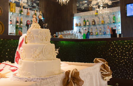 tiered: Three tiered decorated white wedding cake on a table decorated with shoes at an indoor venue with a bar in the background Stock Photo