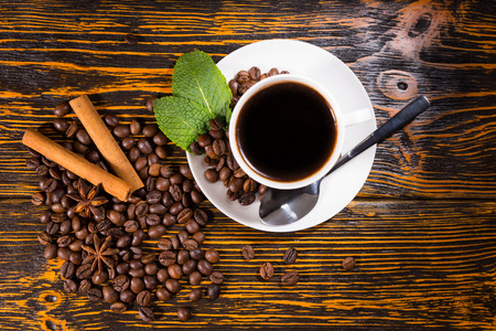 stick of cinnamon: Freshly brewed cup of espresso coffee with roasted whole coffee beans, mint, star anise and stick cinnamon spices on a rustic wooden table, overhead view
