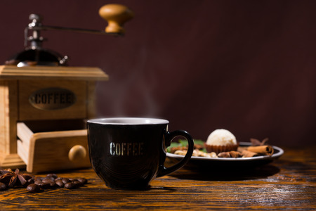 Still Life of Cup of Hot Brewed Coffee on Rustic Wooden Table with Roasted Coffee Beans Beside Hand Grinder and Small Plate with Truffle and Variety of Spice Garnishes