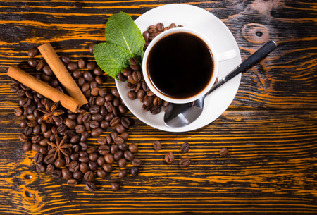 addictive drinking: High Angle Still Life of White Cup and Saucer Containing Fresh Brewed Coffee Resting on Rustic Wooden Table Top Scattered with Roasted Coffee Beans, Cinnamon Sticks and Star Anise Stock Photo