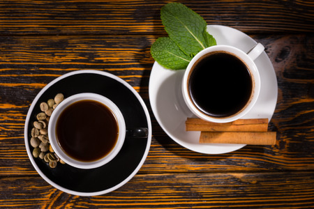 addictive drinking: Top down view on servings of coffee and tea with beans in saucer over dark stained wooden table background Stock Photo