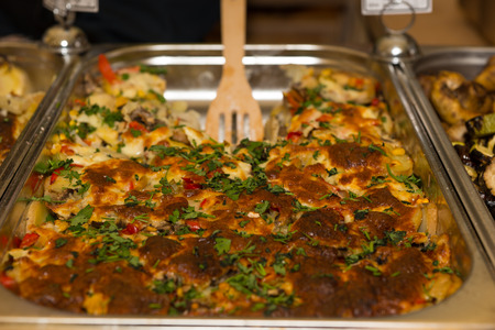 slotted: Close up of stainless steel buffet tray with freshly cooked food and wooden slotted serving spoon