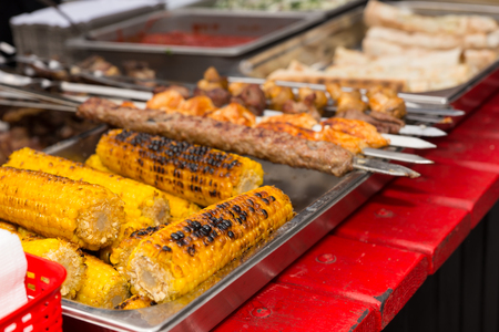 catered: Delicious grilled corn on the cob cooked over a barbecue fire and displayed on a colorful red wooden table at market or a catered event