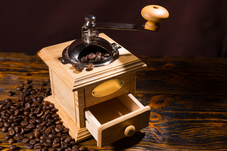 olden day: Single manual square shaped wooden coffee grinder with little open drawer and metal handle over table with dark background and scattered dark beans