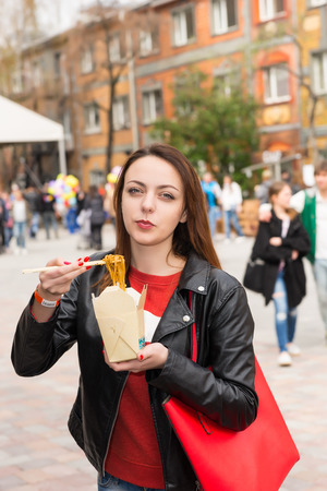 out of the box: Waist Up Portrait of Young Brunette Woman Eating Asian Noodle Cuisine from Take Out Box Using Chopsticks at Busy Outdoor Food Festival in Urban Setting