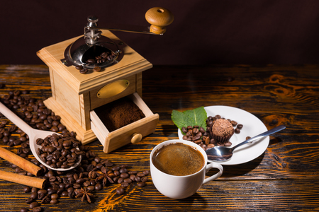 small plate: High Angle Still Life of Cup of Hot Brewed Coffee on Rustic Wooden Table with Roasted Coffee Beans Beside Hand Grinder and Small Plate with Dessert Truffle
