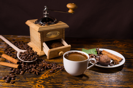 Pile of coffee beans besides open grinder and chocolate drink by a plate of a tasty treat