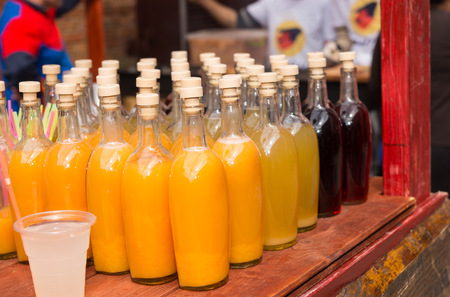unlabelled: Bottles of refreshing homemade orange juice on display at a market on a rustic red wooden stall Stock Photo