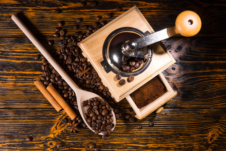 addictive drinking: Top down view on coffee grinder full of finished grounds in drawer, wooden spoon and pair of cinnamon sticks surrounded by beans on table Stock Photo