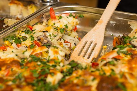 slotted: Close up of freshly baked casserole in stainless steel buffet tray with slotted serving spoon