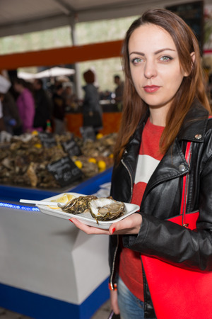 cafeteria tray: Cute young adult woman in black jacket with serious expression holding a tray of baked clams at cafeteria indoors