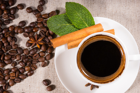 Overhead view of coffee in mug by pile of beans and star anise on light colored canvas
