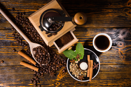small plate: High Angle Still Life of Cup of Hot Brewed Coffee on Rustic Wooden Table Beside Hand Grinder and Small Plate with Truffle and Variety of Spice Garnishes, Surrounded by Scattered Roasted Coffee Beans