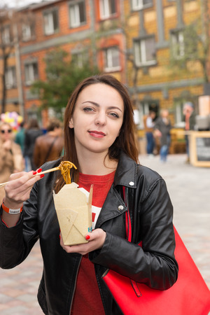 take out: Waist Up Portrait of Young Brunette Woman Eating Asian Noodle Cuisine from Take Out Box Using Chopsticks at Busy Outdoor Food Festival in Urban Setting