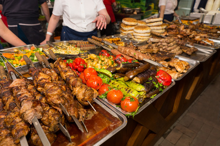 carnes y verduras: Close Up View of Bounty of Cooked Meats and Vegetables Arranged Neatly on Metal Platters with Customers Selecting Items Using Tongs at Restaurant Buffet or Food Festival Foto de archivo