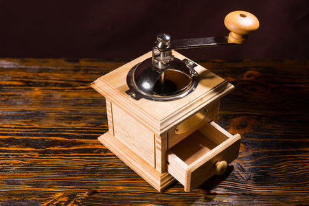 olden day: Square wooden coffee grinder with little open drawer and metal handle over table with dark background Stock Photo