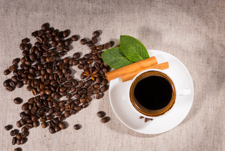 addictive drinking: Overhead view of coffee bean pile by mug decorated with cinnamon sticks and peppermint leaves on canvas