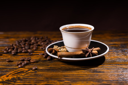Close Up Still Life of White Cup and Saucer Containing Fresh Brewed Coffee Resting on Rustic Wooden Table Top Scattered with Roasted Coffee Beans, Cinnamon Sticks and Star Anise