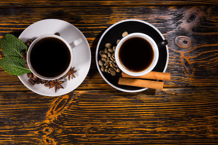Top down view of black tea and coffee garnished with leaves, beans and cinnamon sticks over dark wooden table with copy space Stock Photo