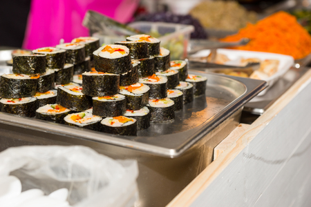 caterers: Close Up Fresh Hand Rolled California Sushi Rolls on Chilled Metal Tray at Restaurant Banquet Buffet