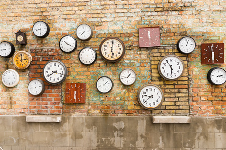 Abstract background composed of numerous round and square clocks on a brick wall