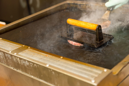 mouth watering: Close Up of Unrecognizable Person Cooking Handmade Hamburgers on Hot Grill Using Metal Spatula and Press in Restaurant or at Food Festival Stock Photo