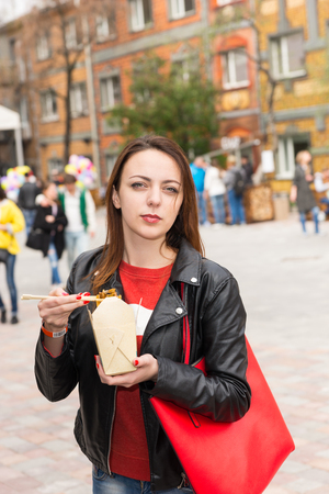 out of the box: Waist Up Portrait of Young Brunette Woman Eating Asian Cuisine from Take Out Box Using Chopsticks at Busy Outdoor Food Festival in Urban Setting