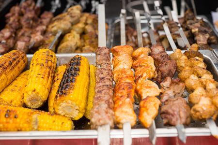 catered: Grilled corn with assorted meat skewers or kebabs fresh from cooking over a barbecue fire on display at a market, buffet or catered event Stock Photo