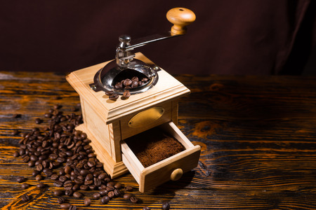 hand crank: Single hand crank square shaped wooden coffee grinder with blank label and drawer full of grounds over table with dark background and scattered dark beans