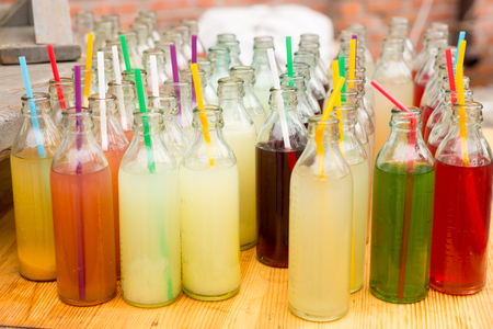 unlabelled: Assortment of fresh fruit juice for sale in opened glass bottles with straws displayed on a market table