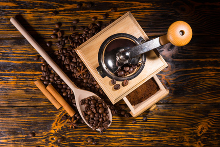 addictive drinking: Top down view on coffee grinder full of finished grounds in drawer, wooden spoon and two cinnamon sticks surrounded by beans on table
