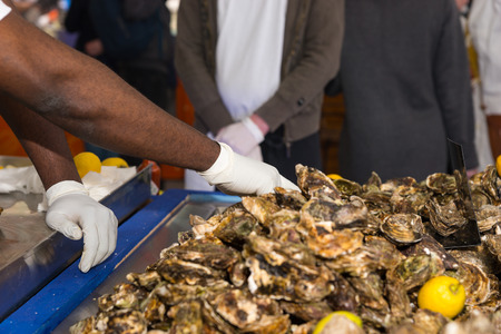 fish vendor: Fish market vendor sorts through shellfish on stainless steel table while customers wait nearby Stock Photo